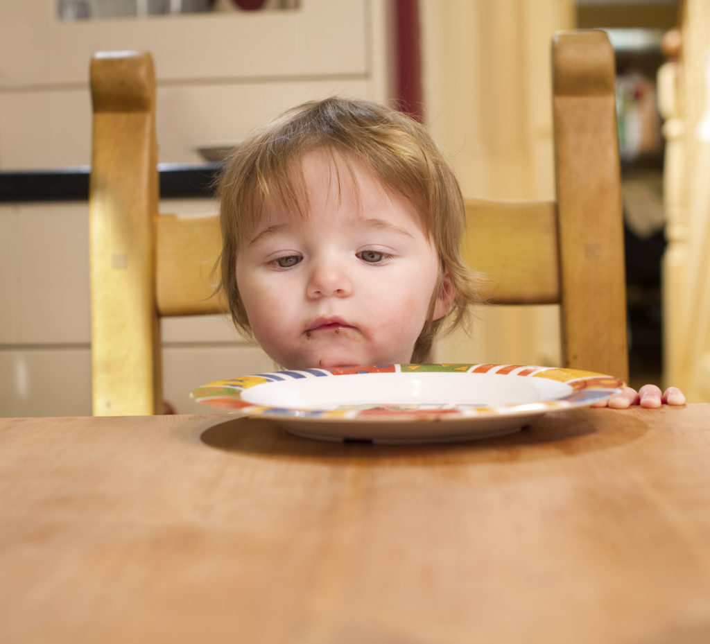 Baby girl with food smeared across her lips looks down at an empty plate.